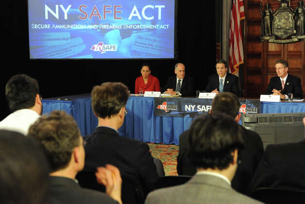 Governor Andrew Cuomo, second from right, holds a press conference at the Capitol about a bill to broaden the state's definition of banned assault weapons, increase penalties for those convicted of gun crimes and create a statewide registry of assault rifles on Monday Jan. 14, 2013 in Albany, N.Y. Sitting with him from the left are Mylan Denerstein, Counsel to the Governor, Larry Schwartz, Secretary to the Governor and Lt. Gov. Robert Duffy. (Lori Van Buren / Times Union) Photo: Lori Van Buren