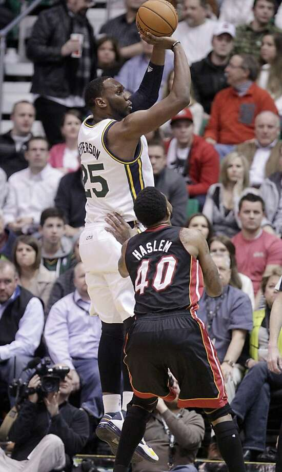 Jazz center Al Jefferson shoots over the Heat's Udonis Haslem in the first quarter of Utah's 104-97 win over Miami. Photo: Rick Bowmer, Associated Press