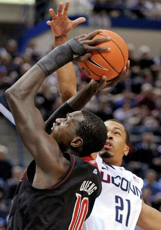 Louisville's Gorgui Dieng, left, is guarded by Connecticut's Omar Calhoun during the first half of an NCAA college basketball game in Hartford, Conn., Monday, Jan. 14, 2013. (AP Photo/Fred Beckham) Photo: Fred Beckham, Associated Press / FR153656 AP