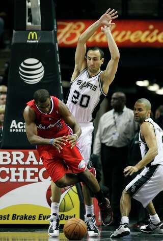 Los Angeles Clippers' Chris Paul (03) get tripped up while driving between Spurs' Manu Ginobili (20) and Tony Parker (09) in the second half of their game at the AT&T Center on Monday, Nov. 19, 2012. Clippers defeated the Spurs, 92-87. Photo: Kin Man Hui, San Antonio Express-News / © 2012 San Antonio Express-News