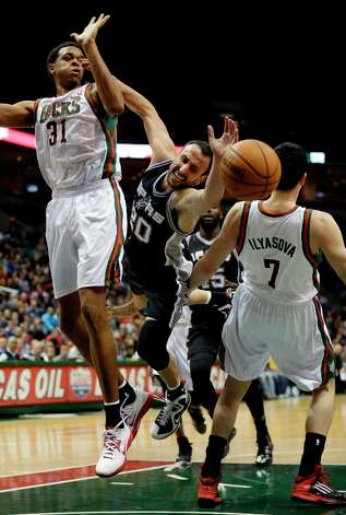 San Antonio Spurs' Manu Ginobili (20) is fouled as he tries to shoot between Milwaukee Bucks' John Henson (31) and Ersan Ilyasova during the second half of an NBA basketball game on Wednesday, Jan. 2, 2013, in Milwaukee. Photo: Morry Gash, Associated Press / AP