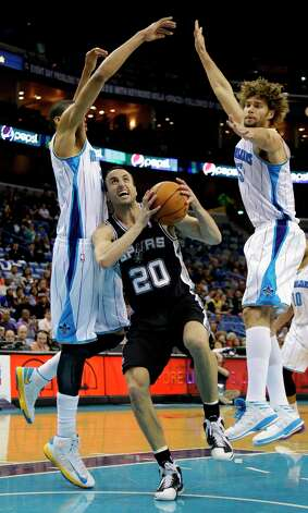 San Antonio Spurs shooting guard Manu Ginobili (20) cuts between New Orleans Hornets power forward Anthony Davis (23), left, and New Orleans Hornets center Robin Lopez (15) in the first half of an NBA basketball game  in New Orleans, Monday, Jan. 7, 2013. Photo: Bill Haber, Associated Press / FR170136 AP