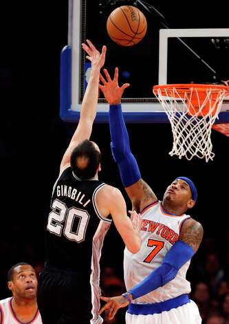 New York Knicks forward Carmelo Anthony (7) defends against a shot by San Antonio Spurs guard Manu Ginobili (20) as Knicks center Marcus Camby, bottom left, watches in the second half of their NBA basketball game at Madison Square Garden in New York, Thursday, Jan. 3, 2013. The Knicks won 100-83. Photo: Kathy Willens, Associated Press / AP