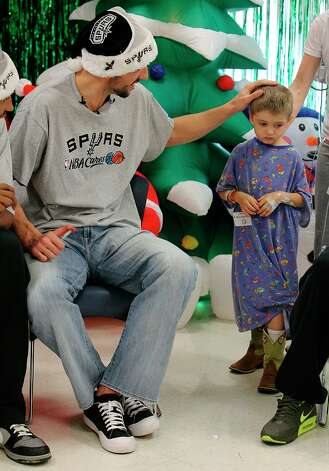 Spurs' guard Manu Ginobili caresses the head of five-year-old Baylor Scott before a photo shoot at the Children's Hospital of San Antonio on Tuesday, Dec. 4, 2012. As an annual affair, the Spurs players met with young hospitalized fans, signed mini-basketballs and posed for photos. A long line trailed into the hallway for a chance for those to meet with Ginobili and teammates Patty Mills and Boris Diaw. Photo: Kin Man Hui, San Antonio Express-News / © 2012 San Antonio Express-News