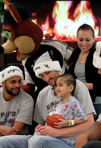 Julian Munoz, 5, sits on the lap of Spurs' guard Manu Ginobili while joined by Spurs' guard Patty Mills, the Spurs Coyote and Munoz's mother, Vanessa Cortinas for a photo at the Children's Hospital of San Antonio on Tuesday, Dec. 4, 2012. As an annual affair, the Spurs players met with young hospitalized fans, signed mini-basketballs and posed for photos. A long line trailed into the hallway for a chance for those to meet with the players. Photo: Kin Man Hui, San Antonio Express-News / © 2012 San Antonio Express-News
