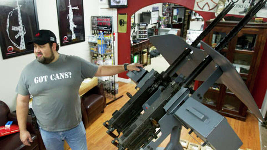Cris Parsons, general manager, stands next to a Browning M-2 twin 50-caliber machine gun, It is for sale for $75,000 at Houston Armory in Stafford. Photo: Brett Coomer, . / © 2013 Houston Chronicle