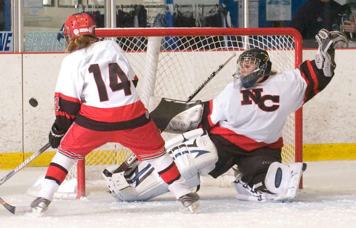 New Canaan's Madzie Carroll and goalie Charlotte Spitzfaden right, defend the goal during a girls hockey game at the Darien Ice Rink in Darien, Conn. on Wednesday, Dec. 23, 2009.
