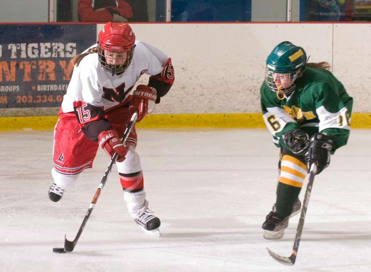 New Canaan's Jana Persky, left, and Hamden's Colleen Murphy, right, during a girls hockey game at the Darien Ice Rink in Darien, Conn. on Wednesday, Dec. 23, 2009.