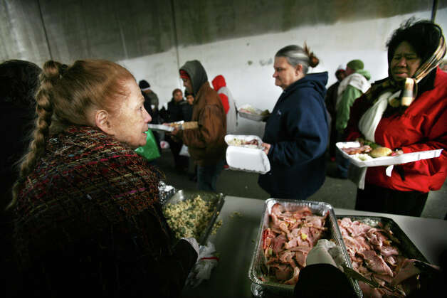 Ann Marie Tarinelli, left, serves her traditional Christmas meal for the needy beneath the John Street viaduct in downtown Bridgeport on Sunday, December 25, 2011. Photo: Brian A. Pounds / Connecticut Post