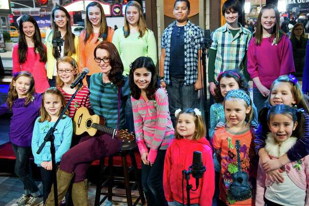 "Ingrid Michaelson accompanied by children from Newtown, Conn. and Sandy Hook Elementary school perform ""Somewhere Over the Rainbow"" on ABC's ""Good Morning America"" on Tuesday, Jan. 15, 2013 in New York.  The Children who survived last month's shooting rampage, recorded a version of ""Over the Rainbow"" to raise money for charity.  They recorded the song at the home of two former members of the Talking Heads rock band. It went on sale Tuesday on Amazon and iTunes, with proceeds benefiting a local United Way and the Newtown Youth Academy. (Photo by Charles Sykes/Invision/AP) Photo: Charles Sykes, Associated Press / Associated Press"