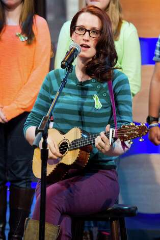 "Ingrid Michaelson accompanied by children from Newtown, Conn. and Sandy Hook Elementary school perform ""Somewhere Over the Rainbow"" on ABC's ""Good Morning America"" on Tuesday, Jan. 15, 2013 in New York. The Children who survived last month's shooting rampage recorded a version of ""Over the Rainbow"" to raise money for charity.  They recorded the song at the home of two former members of the Talking Heads rock band. It went on sale Tuesday on Amazon and iTunes, with proceeds benefiting a local United Way and the Newtown Youth Academy. (Photo by Charles Sykes/Invision/AP) Photo: Charles Sykes, Associated Press / Associated Press"