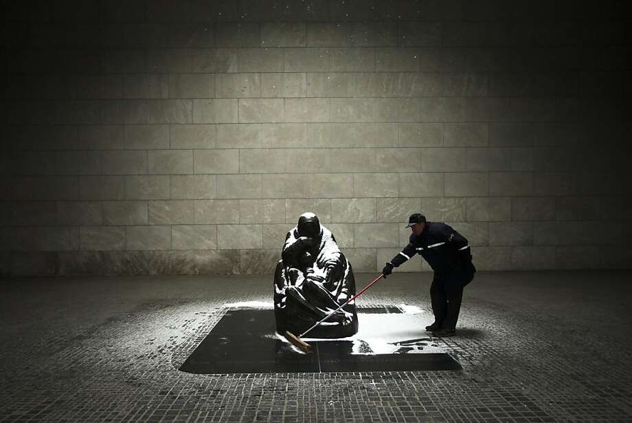 "Cold reminder of war's suffering:In Berlin, a man sweeps snow off the tomb at the Neue Wache (""New Guard House"") of the Central Memorial of the Federal Republic of Germany for the Victims of War and Tyranny. The sculpture by Kathe Kollwitz, ""Mother with her Dead Son,"" is exposed to the elements, symbolizing the pain and hardship of civilians during World War II. Photo: Markus Schreiber, Associated Press"