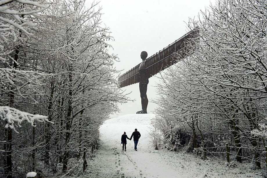 "Snow angel: A couple enjoy a winter stroll near the ""Angel of the North"" statue after a heavy snowfall in Gateshead, England. Photo: Owen Humphreys, Associated Press"