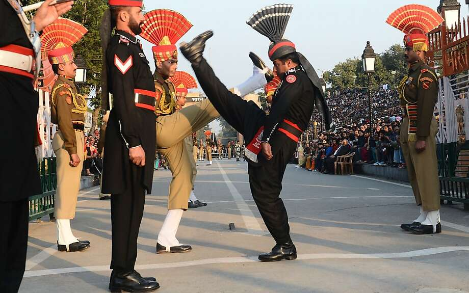 """We shall soon see who the better punter is!Pakistani Rangers (in black) and Indian Border Security Force personnel (in brown) perform the """"flag-off"""" ceremony at the Pakistan-India Wagah Border Post. Indian Prime Minister Manmohan Singh warned that there """"cannot be business as usual"""" with neighboring Pakistan after last week's deadly flare-up along the border in disputed Kashmir. Photo: Arif Ali, AFP/Getty Images"""