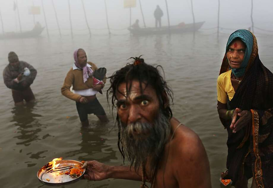An Indian Hindu holy man performs morning prayers for devotees at Sangam, the confluence of the holy rivers Ganges and Yamuna and mythical Saraswati at the Maha Kumbh Mela in Allahabad, India, Tuesday, Jan. 15, 2013. Millions of Hindu pilgrims are expected to take part in the large religious congregation that lasts more than 50 days on the banks of Sangam during the Maha Kumbh Mela in January 2013, which falls every 12th year. (AP Photo/Kevin Frayer) Photo: Kevin Frayer, Associated Press