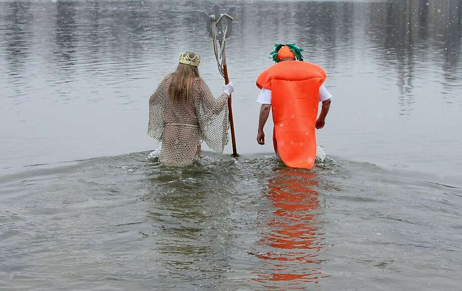 "Eating vegetables is definitely good for you: Swimming in icy water may be good for you. But swimming in icy water with vegetables is just weird. (King Neptune takes a frigid dip with a carrot during the ""Winter Swimming in Berlin"" event at Lake Orankesee.) Photo: Adam Berry, Getty Images"