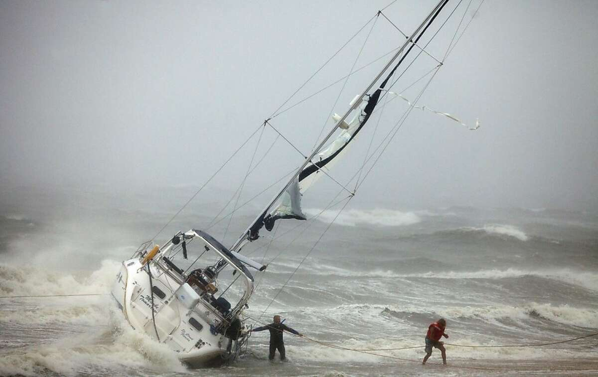 FILE - In this Aug. 27, 2011 file photo, one of two people rescued from a sailboat, right, uses a line to make their way onto the beach on Willoughby Spit in Norfolk, Va., after a couple and their cat were rescued from the boat that foundered in the waters of the Chesapeake Bay battered by winds from Hurricane Irene. Nature is pummeling the United States in 2011 with extremes. There have been more than 700 U.S. disaster and weather deaths. What's happening, say experts, is mostly random chance or the bad luck of getting the wrong roll of the dice. However, there is something more to it, many of them say. Man-made global warming is loading the dice to increase our odds of getting the bad roll. (AP Photo/TheVirginian-Pilot, Bill Tiernan, File) MAGS OUT