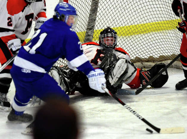 Darien's #21 Brendan Hathaway tries to line up a shot as a prone Fairfield Warde/Ludlowe goalie Connor Frawley tracks him, during boys hockey action at the Wonderland of Ice in Bridgeport, Conn. on Saturday January 12, 2013. Photo: Christian Abraham / Connecticut Post