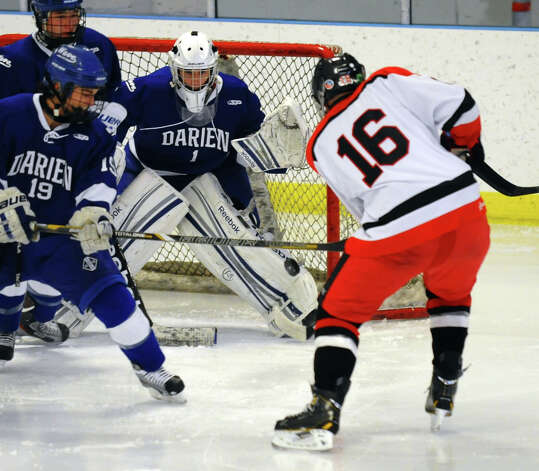 Darien goalie #1 Michael Colon tracks a shot attempt by Fairfield Warde/Ludlowe's #16 Matthew Larouche, during boys hockey action at the Wonderland of Ice in Bridgeport, Conn. on Saturday January 12, 2013. Photo: Christian Abraham / Connecticut Post