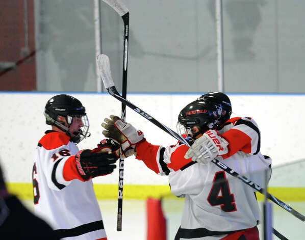 Teammates rush in to celebrate a goal by Fairfield Warde/Ludlowe's #11 Kevin Robinson, during boys hockey action against Darien at the Wonderland of Ice in Bridgeport, Conn. on Saturday January 12, 2013. Photo: Christian Abraham / Connecticut Post