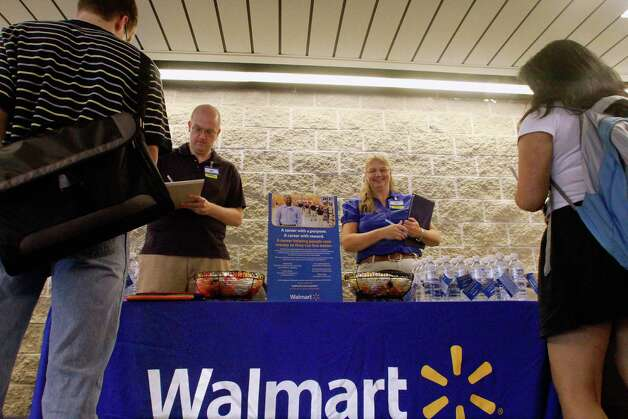 In this Thursday, Sept. 1, 2011, photo, Wal-Mart employees Jon Christians and Lori Harris take job applications and answers questions during a job fair at the University of Illinois Springfield campus in Springfield, Ill.  Wal-Mart Stores Inc., the world's largest retailer and nation's largest private employer, said Tuesday, Jan. 15, 2013, it is making a pledge to boost its sourcing from domestic suppliers and hire more than 100,000 veterans. The plans were to be announced as part of an address by Bill Simon, president and CEO of Wal-Mart's U.S. business, at an annual retail industry convention in New York. (AP Photo/Seth Perlman) Photo: Seth Perlman, Associated Press / AP