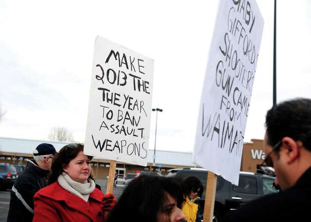 Jen Sage-Robison, of Bethel, holds a sign outside the Walmart in Danbury, Conn. Tuesday, Jan. 15, 2013 during a protest to deliver a petition signed by more than 250,000 Walmart customers and concerned citizens nationwide urging the retail giant to stop the sale of assault weapons and munitions. Photo: Autumn Driscoll / Connecticut Post