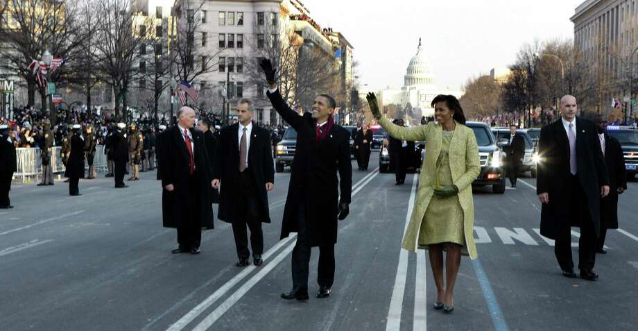FILE - This Jan. 20, 2009 file-pool, photo shows President Barack Obama and first lady Michelle Obama waving as they walk down Pennsylvania Avenue en route to the White House from the Capitol in Washington. At some point on Inauguration Day, if all goes expected, the president's limousine will slow to a stop on its journey down Pennsylvania Avenue from the Capitol to the White House. A Secret Service agent will open the rear passenger door, and the newly sworn-in president will emerge from his car for a several-minute stroll. The crowd will cheer. The president will wave. In that moment, Pennsylvania Avenue is America's red carpet. And the president is the only celebrity on it. The victory walk has become an iconic inaugural moment, one expected by the public and the press.  And though the tradition dates only to President Jimmy Carter, it has already developed an air of inevitability and predictable patterns.   (AP Photo/Doug Mills, File, Pool) Photo: Doug Mills, Associated Press / AP