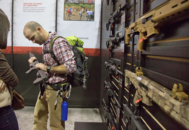 Will Michaels of Homer, La., examines a Bushmaster M4 A3 Carbine 300 AAC Blackout rifle at the Bushmaster exhibit during the Shooting Hunting Outdoor Tradeshow, Tuesday, Jan. 15, 2013, in Las Vegas. Michaels, who owns a sporting goods store, said while his gun sales focus primarily on bolt action hunting rifles, he and his clients have taken an interest in assault rifles over the last five years because of an expanding wild hog problem in his region. The National Shooting Sports Foundation was focusing its 35th annual SHOT Show on products and services new to what it calls a $4.1 billion industry, with a nod to a raging national debate over assault weapons. Photo: Julie Jacobson, AP / AP