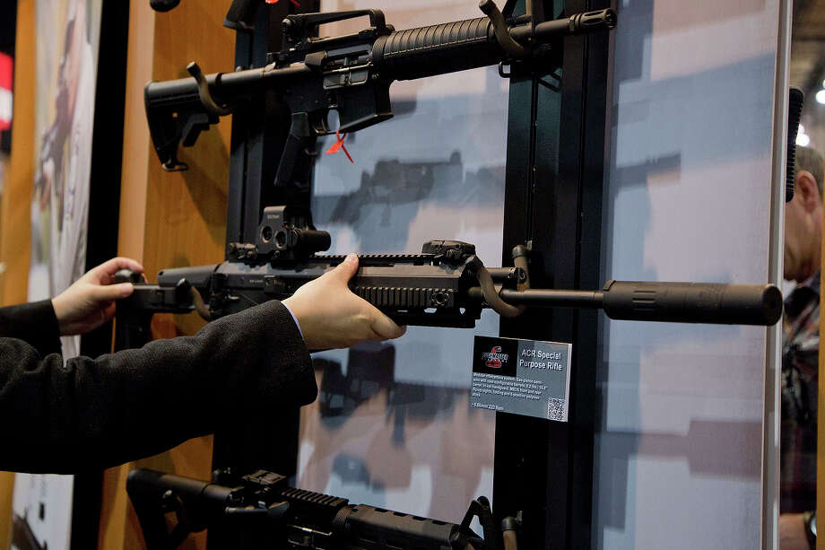 Accessories manufacturer Kevin Kao, of Irvine, Calif., examines a military grade Remington ACR Special Purpose Rifle at the 35th annual SHOT Show, Tuesday, Jan. 15, 2013, in Las Vegas. The National Shooting Sports Foundation was focusing its 35th annual SHOT Show on products and services new to what it calls a $4.1 billion industry, with a nod to a raging national debate over assault weapons. Photo: Julie Jacobson, AP / AP