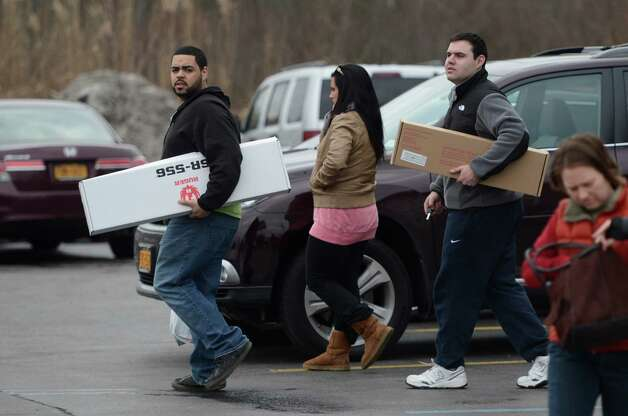 Thomas Gonzalez, left, and Ben Levine, right, leave Zack's Sports store carrying newly purchased firearms Tuesday morning, Jan. 15, 2013 in Round Lake, N.Y. Lawmakers are on the verge of passing new more restricting gun. (Skip Dickstein/Times Union) Photo: SKIP DICKSTEIN / 00020773A