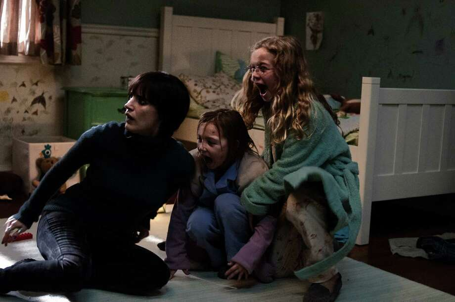 "(L to R) Annabel (JESSICA CHASTAIN) tries to protect Lilly (ISABELLE NƒLISSE) and Victoria (MEGAN CHARPENTIER) in ""Mama"", a supernatural thriller presented by Guillermo del Toro that tells the haunting tale of two little girls who disappeared into the woods the day that their parents were killed. When they are rescued years later and begin a new life, they find that someone or something still wants to come tuck them in at night. Photo: George Kraychyk, Universal Pictures / ONLINE_YES"