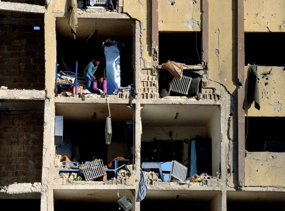 In this photo from the official news agency SANA, survivors and rescue workers in Aleppo, northern Syria, gauge the damage to a university building caused by one of two explosions that rocked the campus Tuesday. Photo: HOPD / SANA
