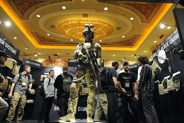 Conventioners browse through the booth of military performance gear maker Crye Percision of Brooklyn, NY.  SHOT Show, the world's largest gun show, opened at the Sands Convention Center in Las Vegas, NV on Tuesday January 15th, 2013, where an estimated 60,000 industry enthusiasts are expected to attend. Photo: Michael Short, Special To The Chronicle