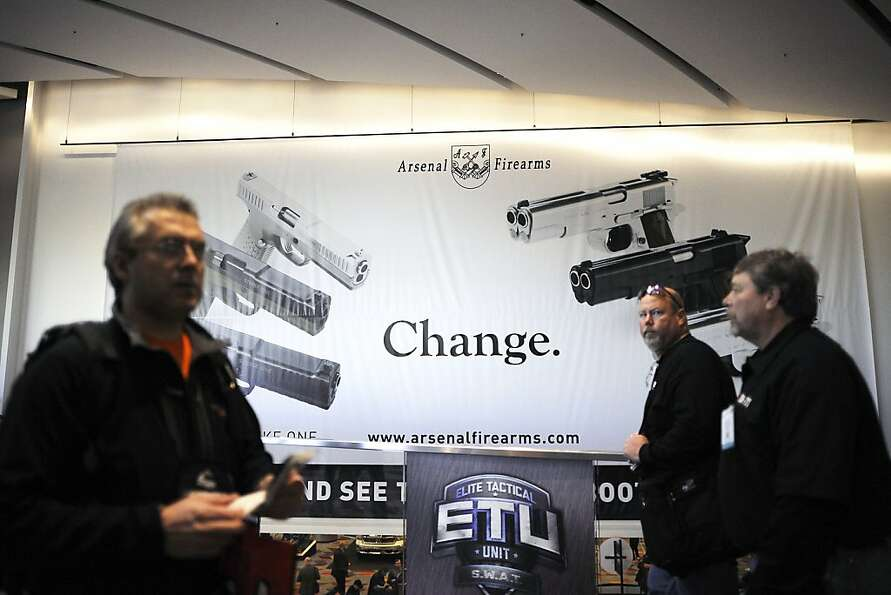 Gun show attendees walk past a large banner for Arsenal Firearms in the lobby of the convention cent