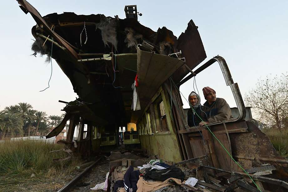 Workers remove the wreckage of a train carrying young conscripts that crashed about 25 miles south of Cairo, killing at least 19 and injuring 105. Photo: Khaled Desouki, AFP/Getty Images