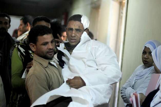 An injured Egyptian is carried by a relative at a hospital following a train crash in Badrasheen, 40 KM South Cairo, Egypt, Tuesday, Jan. 15, 2013. At least 19 people died and more than 100 were injured when two railroad passenger cars derailed just south of Cairo, health officials say. The accident comes less than two weeks after a new transportation minister was appointed to overhaul the rail system, and just two months after a deadly collision between a train and school bus. (AP Photo/Amr Nabil) Photo: Amr Nabil, Associated Press