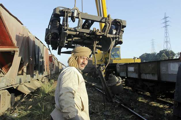 Egyptian worker remove wreckage from the site of a train accident in Badrasheen, 40 KM south of Cairo, Egypt, Tuesday, Jan. 15, 2013. At least 19 people died and more than 100 were injured when two railroad passenger cars derailed just south of Cairo, health officials say. The accident comes less than two weeks after a new transportation minister was appointed to overhaul the rail system, and just two months after a deadly collision between a train and school bus. (AP Photo/Amr Nabil) Photo: Amr Nabil, Associated Press