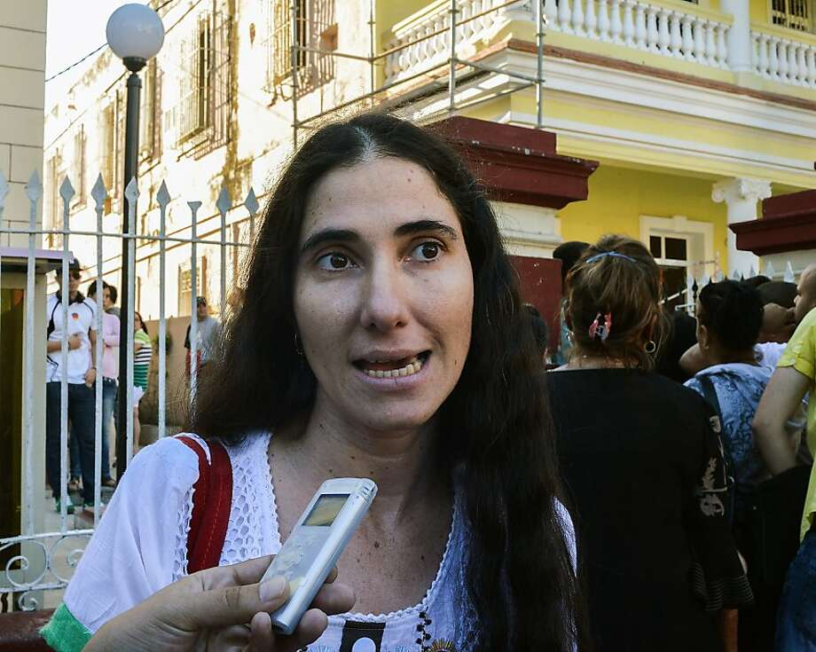 Cuban opposition blogger Yoani Sanchez speaks with the press outside a Migration Office, on January 14, 2013 in Havana. A law allowing Cubans to travel abroad without special exit visas took effect on the communist-ruled island for the first time in half a century. The measure does away with the exit visas that have kept most Cubans from ever traveling abroad.   AFP PHOTO/ADALBERTO ROQUEADALBERTO ROQUE/AFP/Getty Images Photo: Adalberto Roque, AFP/Getty Images