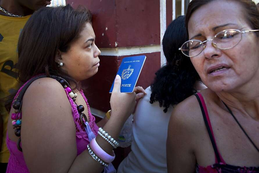 A woman holding her Cuban passport lines up with others at a migration office in Havana, Cuba, Monda