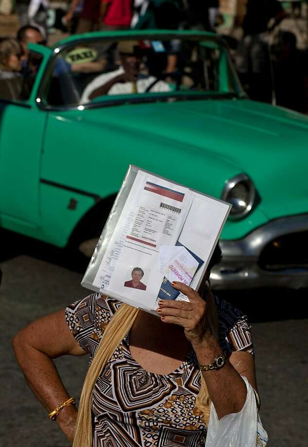 A woman shades herself with her documents as she waits outside the U.S. Interests Section to apply for U.S. visas in Havana, Cuba, Monday, Jan. 14, 2013. Cubans formed long lines outside travel agencies and migration offices, as a highly anticipated new law took effect Monday, ending the island's much-hated exit visa requirement.  In October, the Interests Section more than doubled its capacity for processing nonimmigrant visa applications, and the wait time for an interview has fallen from nearly five years to less than a year, according to U.S. diplomats. (AP Photo/Ramon Espinosa) Photo: Ramon Espinosa, Associated Press