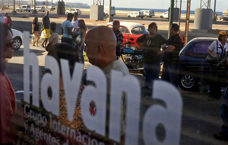 People wait in a line that continues on to the sidewalk, to buy plane tickets at a small travel agency in Havana, Cuba, Monday, Jan. 14, 2013. Cubans formed long lines outside travel agencies and migration offices on Monday, as a highly anticipated new law took effect ending the island's much-hated exit visa requirement. (AP Photo/Ramon Espinosa) Photo: Ramon Espinosa, Associated Press