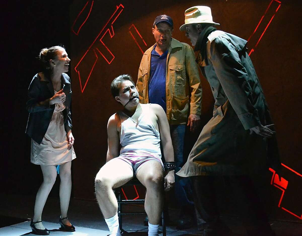 Zamir (Sal Mattos, center, seated) is interrogated by his super-patriot new father-in-law Leonard (Paul Stout, center rear) and his helpers Hildegarde (Teri Whipple, left) and Looney Tunes (Christopher P. Kelly) in Christopher Durang's