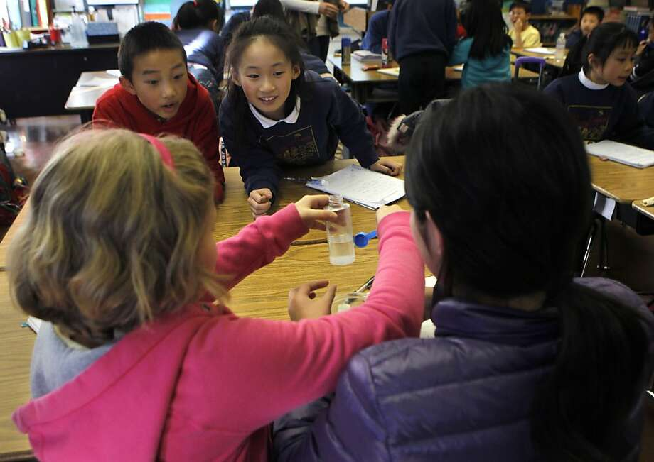 Otto Gin and Anita Liu (top) watch classmates Ema Bajrani (lower left) and Kelly Lai combine salt and water for a science experiment in Melissa Thormahlen's 4th and 5th grade class at John Yehall Chin Elementary School in San Francisco, Calif. on Tuesday, Jan. 15, 2013. Photo: Paul Chinn, The Chronicle