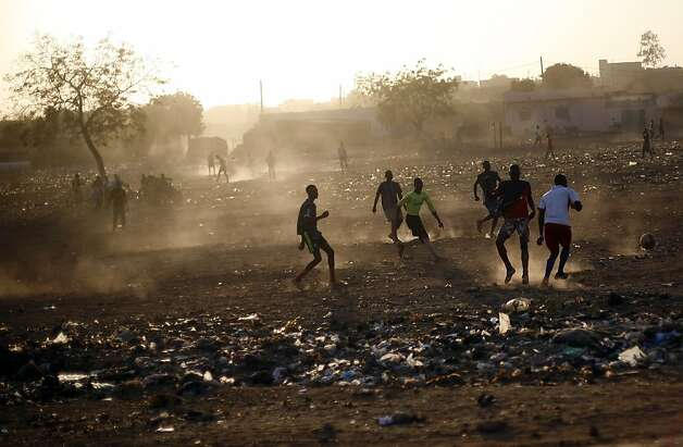 Young men play football in Bamako, Mali, Tuesday Jan. 15, 2013. French forces led an all-night aerial bombing campaign Tuesday to wrest control of a small Malian town from armed Islamist extremists who seized the area, including its strategic military camp. A a convoy of 40 to 50 trucks carrying French troops crossed into Mali from Ivory Coast as France prepares for a possible land assault. Several thousand soldiers from the nations neighboring Mali are also expected to begin arriving in coming days. (AP Photo/Jerome Delay) Photo: Jerome Delay, Associated Press