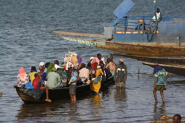 Passengers board a commuter boat, on the Niger river, in Segou, central Mali, Tuesday, Jan. 15, 2013. After a punishing bombing campaign failed to stop the southward advance of al-Qaida-linked fighters, France announced Tuesday that it is tripling the number of troops deployed to Mali, strongly suggesting that French forces are preparing for a land assault to dislodge the extremists. Over the weekend, the rebels made their way to the rice-growing region just north of the main city in central Mali, Segou. The rebels cut across in a knifing movement, first cutting in through the road connecting Diabaly, home to an important military camp and a population of 35,000, and Niono, the last town before Segou.(AP Photo/Harouna Traore) Photo: Harouna Traore, Associated Press