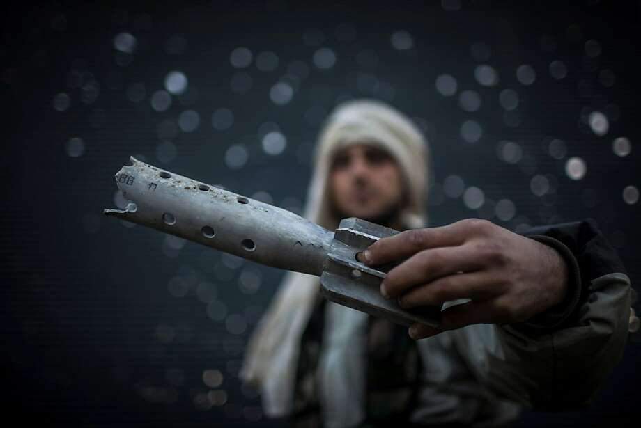 A Free Syrian Army fighter displays a damaged ordinance in Aleppo, Syria, Tuesday, Jan. 15, 2013. Two explosions struck the main university in the northern Syrian city of Aleppo on Tuesday, causing an unknown number of casualties, state media and anti-government activists said. (AP Photo/Andoni Lubaki) Photo: Andoni Lubaki, Associated Press