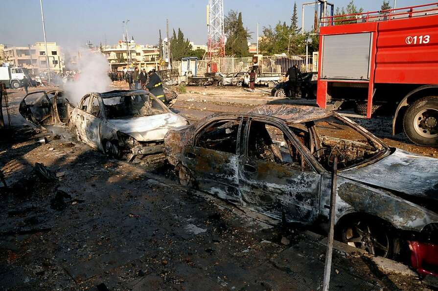 In this photo released by the Syrian official news agency SANA, damages cars are seen after an explo