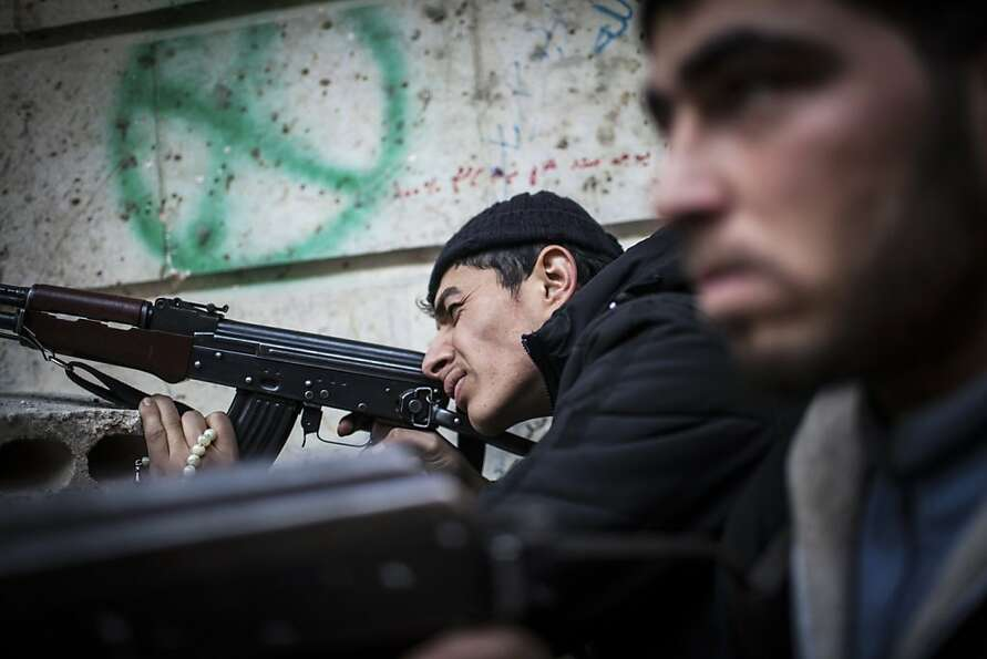 A Free Syrian Army fighter aims his weapon in Aleppo, Syria, Tuesday, Jan. 15, 2013. Two explosions