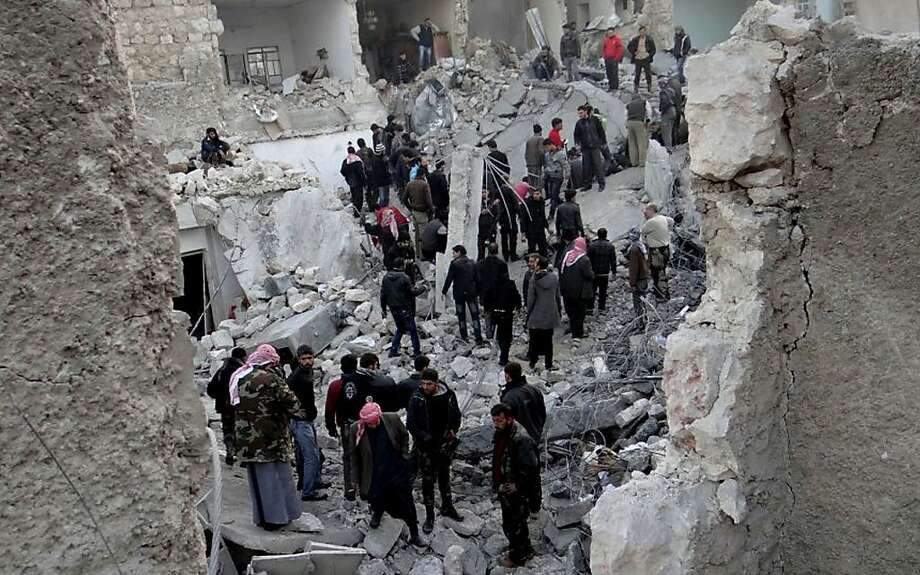In this citizen journalism image taken on Monday, Jan. 14, 2013, provided by Aleppo Media Center AMC which has been authenticated based on its contents and other AP reporting, people gather around destroyed buildings after airstrikes that targeted Aleppo, Syria. (AP Photo/Aleppo Media Center AMC) Photo: Hoep, Associated Press