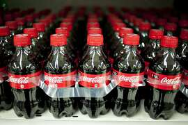 Bottles of Coca-Cola Co. soda sit on display in a supermarket in Princeton, Illinois, U.S., on Friday, Oct. 12, 2012. Coca-Cola Co. is scheduled to release earnings data on Oct. 16. Photographer: Daniel Acker/Bloomberg